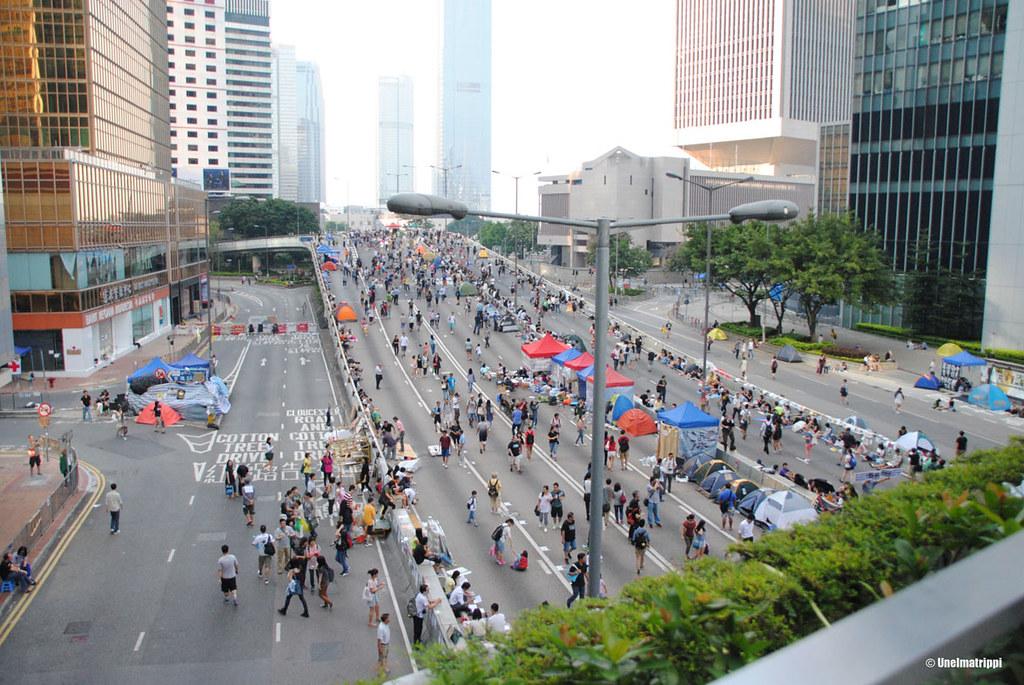 Mielenosoittajia autoista tyhjennetyillä kadulla