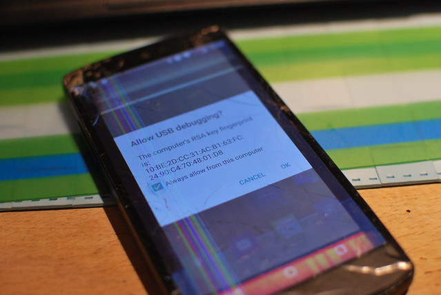 A Nexus 5 phone with a broken screen, showing a USB debugging authorization dialog