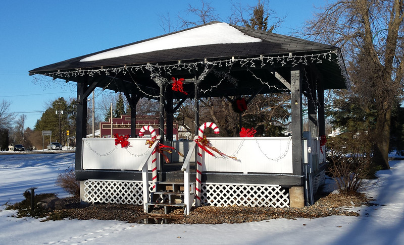 sunny photo of a gazebo with lights and two large candy canes