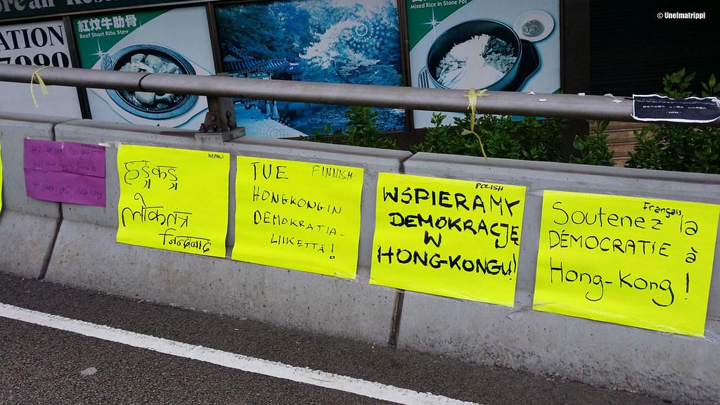 Demokratialiikettä tukevia lappuja sillalla, mukana myös suomenkielinen lappu