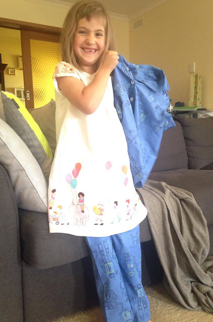 A child wears a dress and pyjama pants. She holds up a pyjama top excitedly.