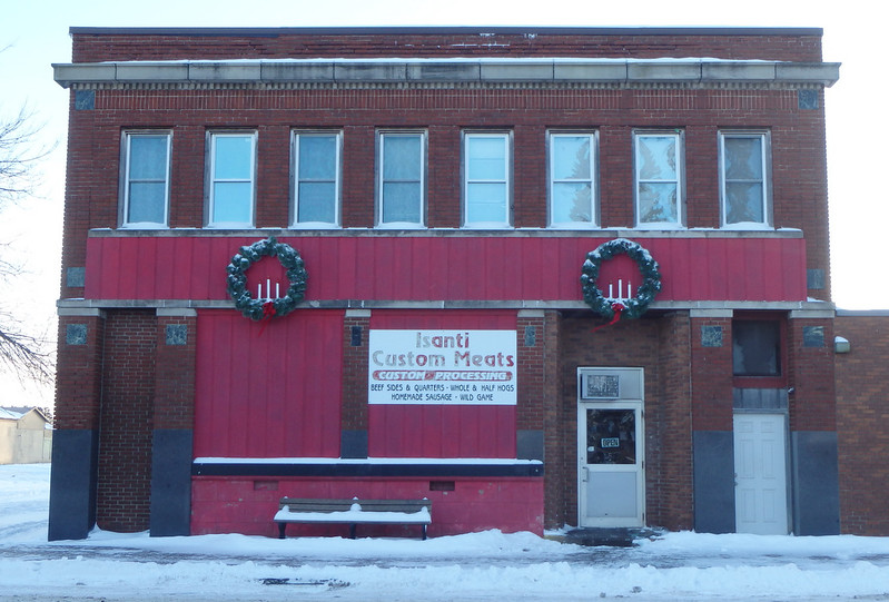 Isanti Custom Meats with two large snow-covered wreaths