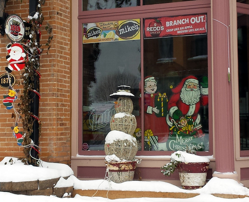 painted images in the window, with another Santa sliding down a lamppost outside