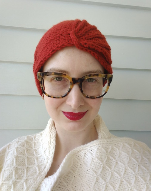 A woman wears a red cloche and white scarf.