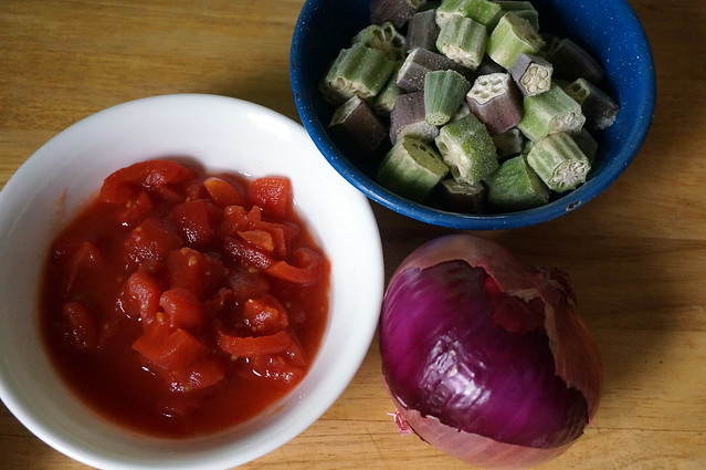 A small white bowl of canned tomatoes, a blue enamel bowl of frozen okra, and a bright purple onion: winter cooking necessities, clustered on a countertop.