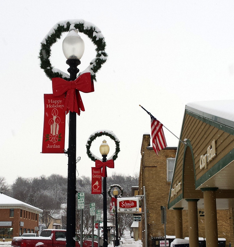 a row of three wreaths at the top of the lamp posts, with the lamp in the center