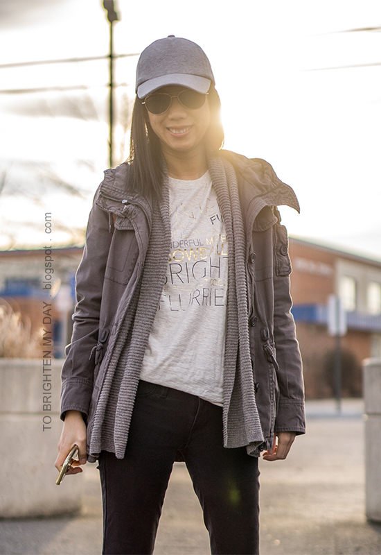 light gray baseball cap, gray military jacket, taupe open cardigan, winter graphic tee, black skinny jeans