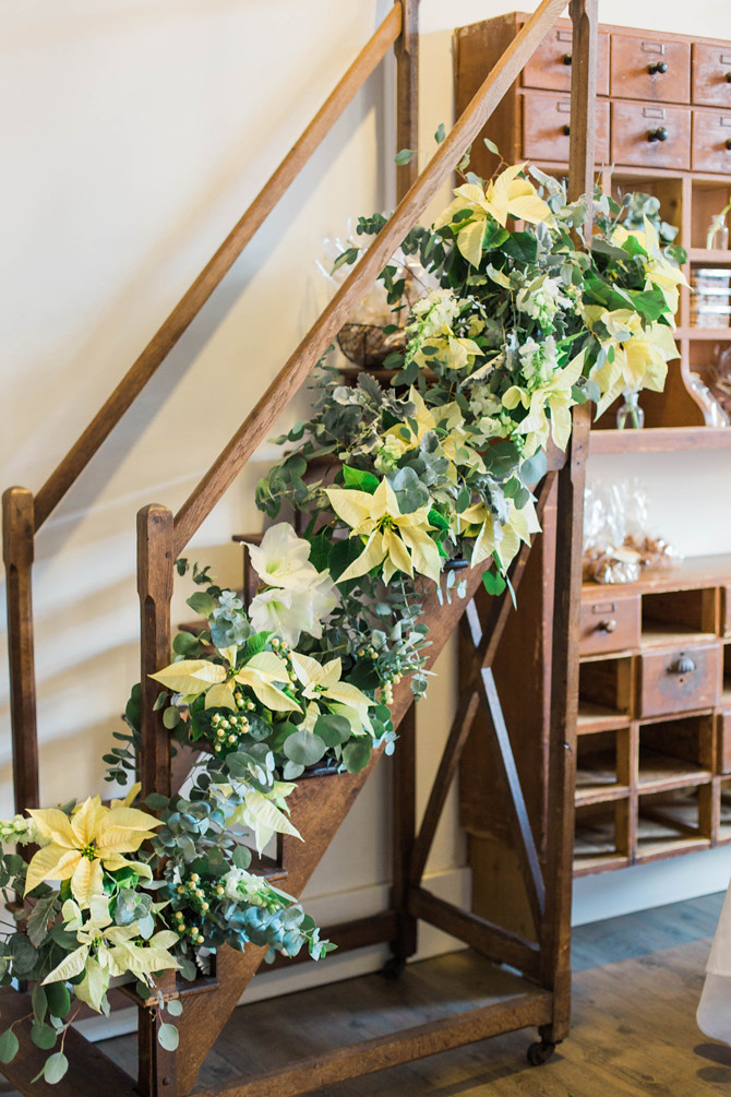 fresh flower pointsettia eucalyptus holiday party stairs garland