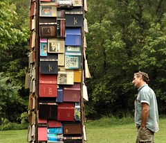tower of books and a man interested | by zen