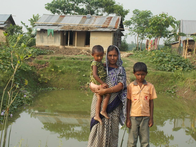 Suchana beneficiary Hasna begum with her Children will better utilize their Homestead Pond for improving consumption and income through increased production. Photo by Md. Badrul Alam.