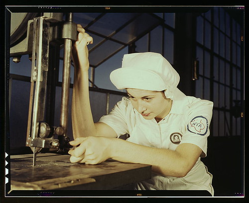 """Women in white"" doctor Navy planes (motors) at the Naval Air Base, Corpus Christi, Texas. Mildred Webb, an NYA trainee at the base, is learning to operate a cutting machine in the Assembly and Repair Department. After about eight weeks as an apprentice s 