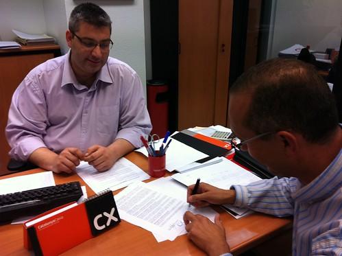 En oficina caixa catalu a firmando convenio ayuda a for Caixa oficina internet
