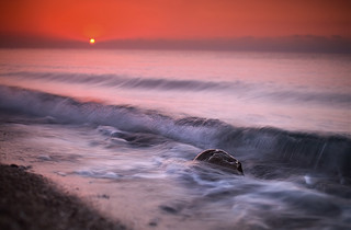 landscape with shallow depth of field sunrise over the sea with a stone and waves | by czdistagon.com