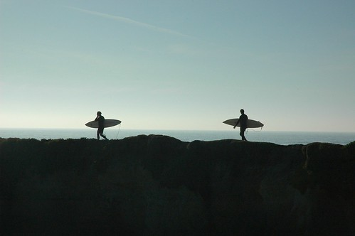 Two men carrying surf boards, wearing wet suits, on the cliff overlooking the Pacific Ocean on a clear sunny day, Santa Cruz, California, USA | by Wonderlane