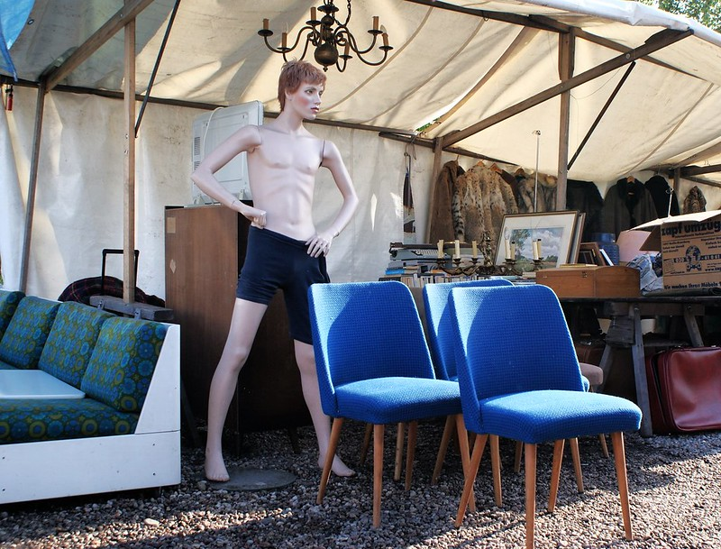 > Des chaises bleues et un mannequin maigre.