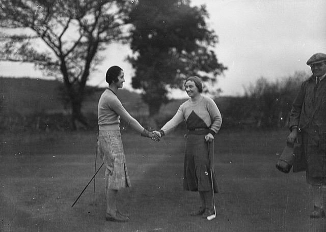 Two lady golfers shaking hands