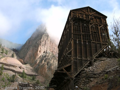 Mist rises behind old mining buildings and mines along the Bachelor Historic Loop near Creede, Colorado