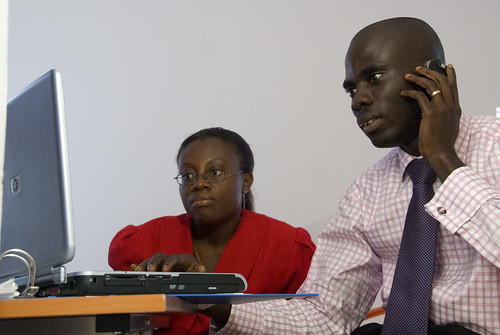 Colleagues look at information on a computer screen | by World Bank Photo Collection