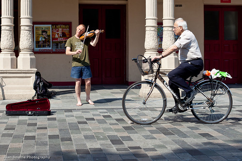 Elder cyclist and the barefoot fiddler | by Alan Bourne