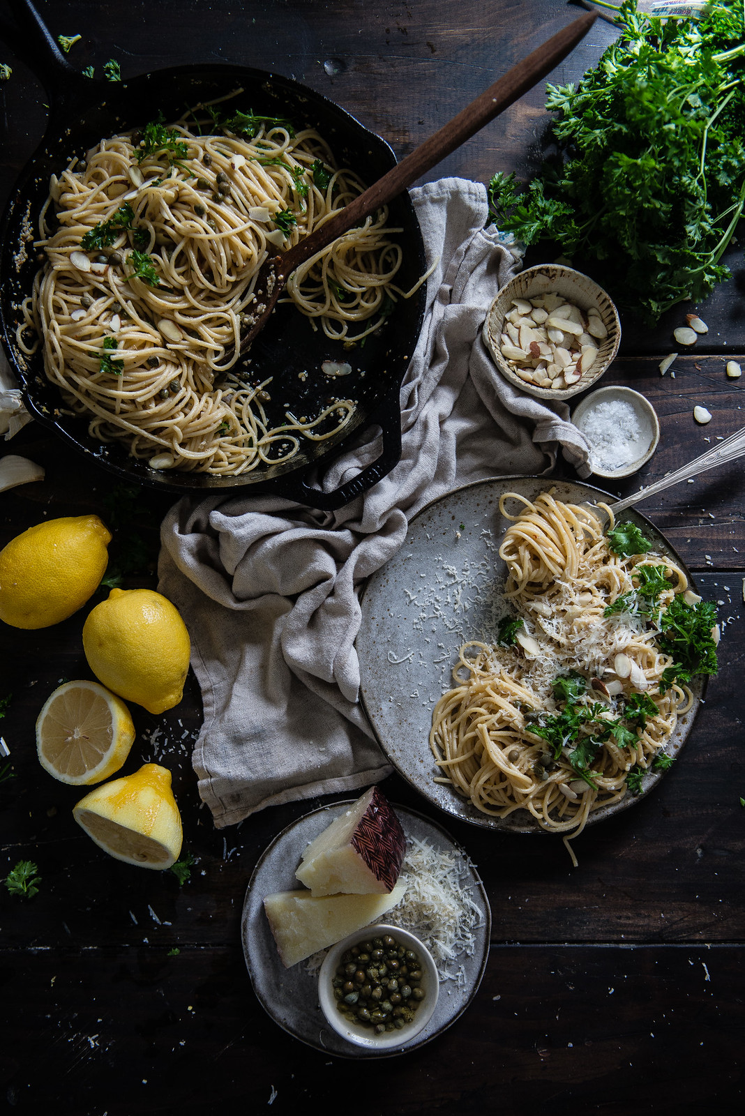 garlicky spaghetti with lemon, capers, & almonds   two red bowls