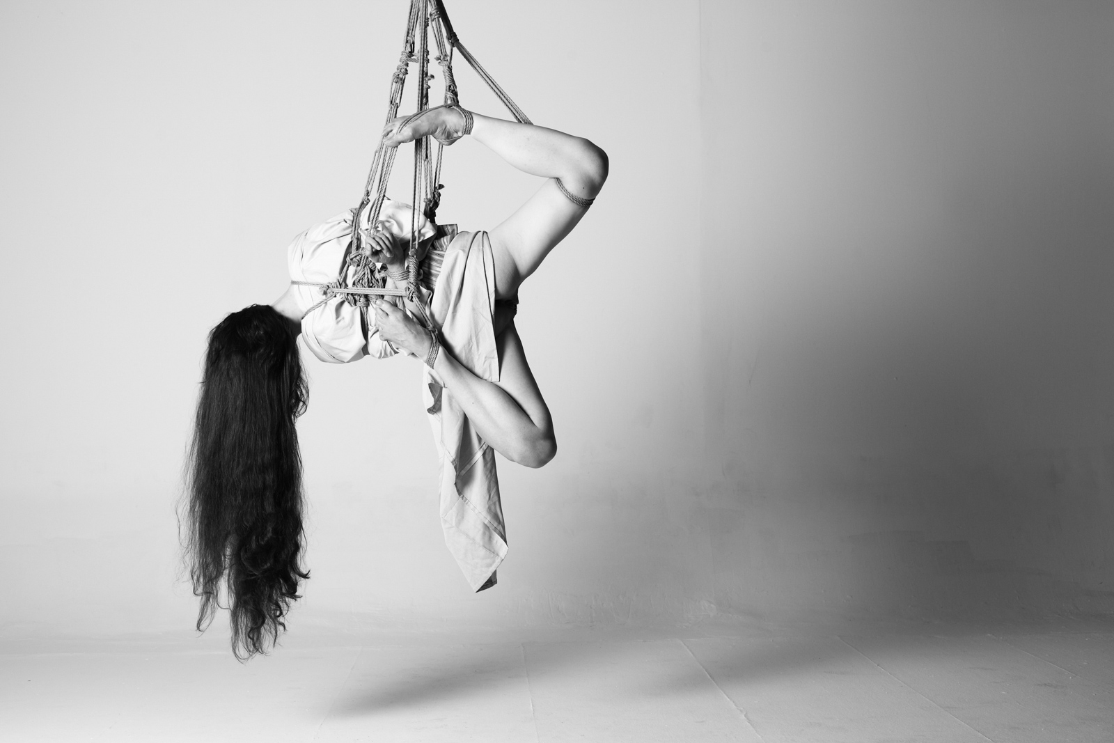 woman with long dark hair wearing a kimono tied in a shibari yoko-zuri side suspension