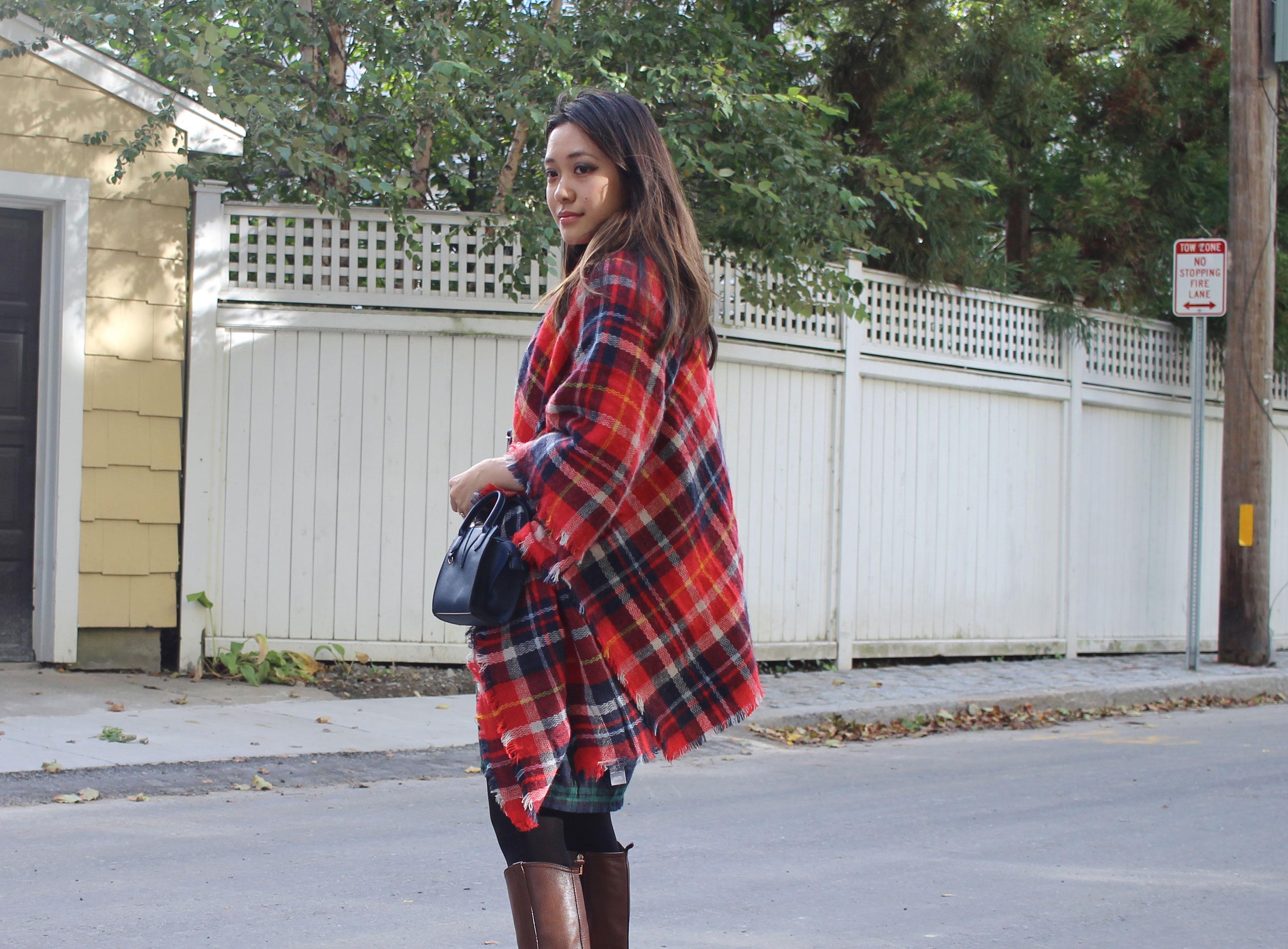 Red plaid scarf worn as shawl