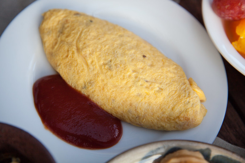 Freshly made omelette (filled with bacon, onion, mushroom) with a side of ketchup