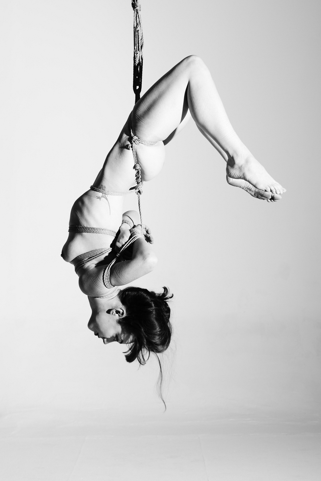 silhouette of a man standing next to a woman tied in shibari suspension
