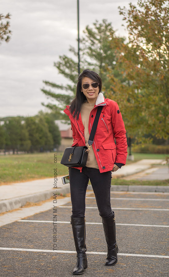 red performance jacket, camel tunic sweater, black skinny jeans, black crossbody bag, black riding boots