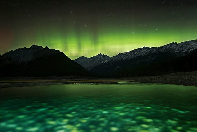 """Green Dream"" The aurora borealis rises above the peaks of Jasper National Park on a stunning night in the mountains. I plunged by headlamp into the Maligne River to add the foreground a little more punch. Thanks to Jeff Wallace Photography, Lee Nordbye P"