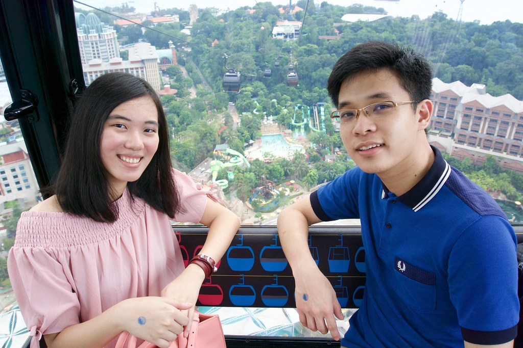 Joshua & Tiffany on the cable car with Sentosa Island on the background.