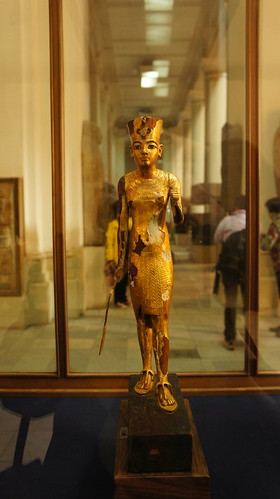 A small golden statue showing king Tut wearing sandals
