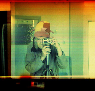 reflected self-portrait with Zeiss Ikon Ikomatic A camera and hat with plaits