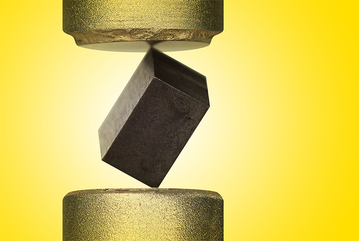 Rectangular piece of plutonium pinned between two cylinders of acoustic transducers