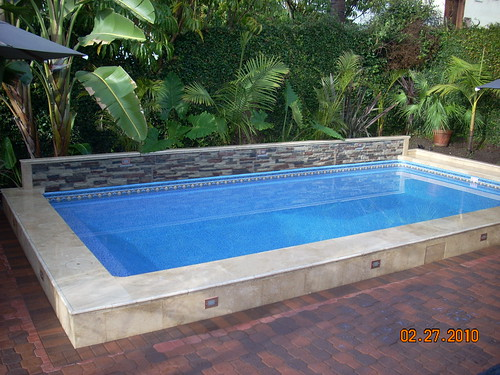 Secard pools custom islander pool with tile finish and rai for Swimming pool design jobs
