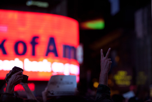 An Occupy Wall Street protestor holds up a peace sign with the Times Square Bank of America sign in the background. | by TenSafeFrogs