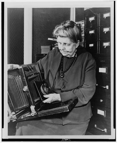 [Frances Benjamin Johnston, three-quarter length portrait, holding and looking down at camera, facing slightly left] (LOC) | by The Library of Congress