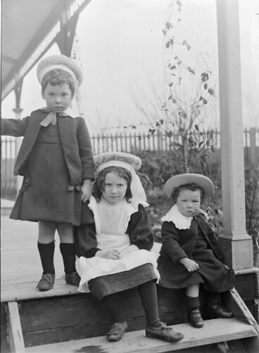Three children on veranda steps | by State Library Victoria Collections