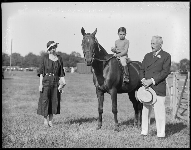 Grafton Smith with woman and boy on horse holding trophy