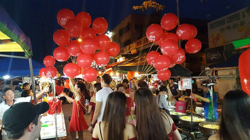 The H.O.T Team distributing balloons in night market.