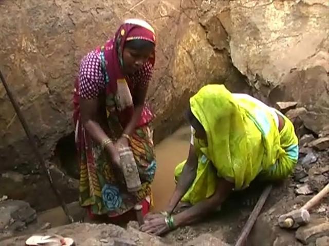 कुएँ का पत्थर तोड़ती महिलाएँ