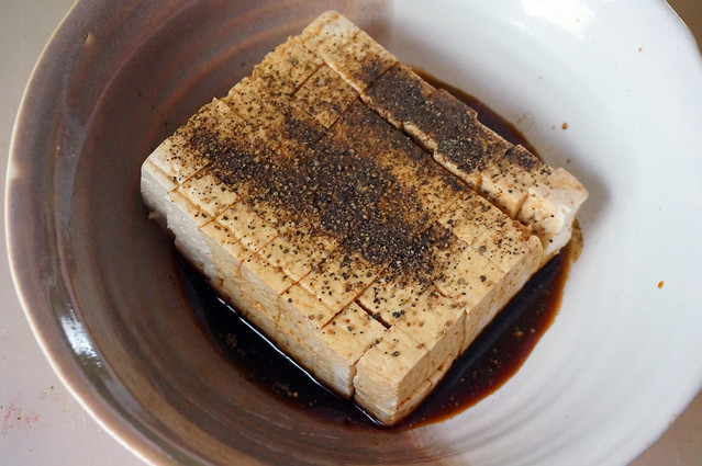 A block of tofu, cubed but still formed into a large rectangle, sitting in a brown and white ceramic bowl. The tofu is dark brown from the soy sauce drizzled all over it, and has a solid layer of pepper sprinkled over the top.