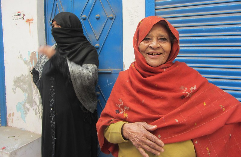 Shehnaaz (in burqa) turns around to get photographed as Shamila Begum, with ochre shawl, laughs at her in a narrow lane at Seelampur.</body></html>
