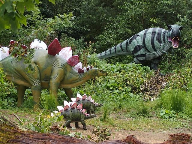 Tyrannosaurus Rex terrorising a family of Stegosaurus