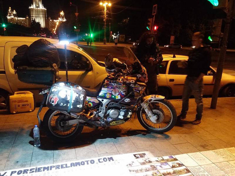 Путешественник рядом со своим мотоциклом