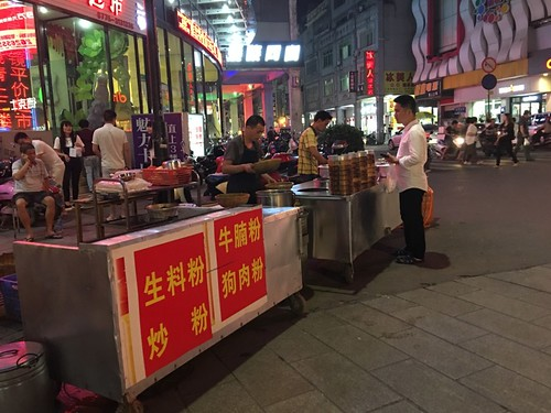 Mobile vendors on commercial pedestrian street in downtown (dog meat noodle on its menu)