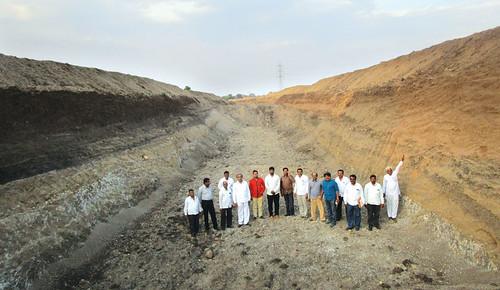 हरंगुल ग्रामवासी अपने द्वारा गहरी खोदी गई सूखी धारा में खड़े हैं