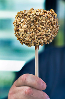 Man holding a caramel apple with nuts. photo by Jackie Alpers | by Jackie Alpers