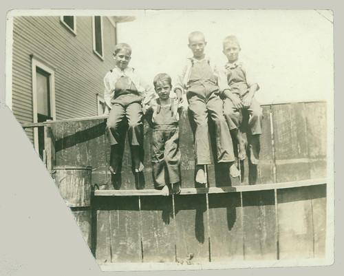 Four boys on a fence
