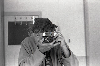 reflected self-portrait with Taron Eyemax camera and hat with bells on